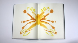 Yellow and orange inkblot on facing journal pages.