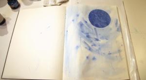 Blue metallic paper circle glued on journal page.