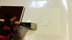Spreading glue on the back of the page.